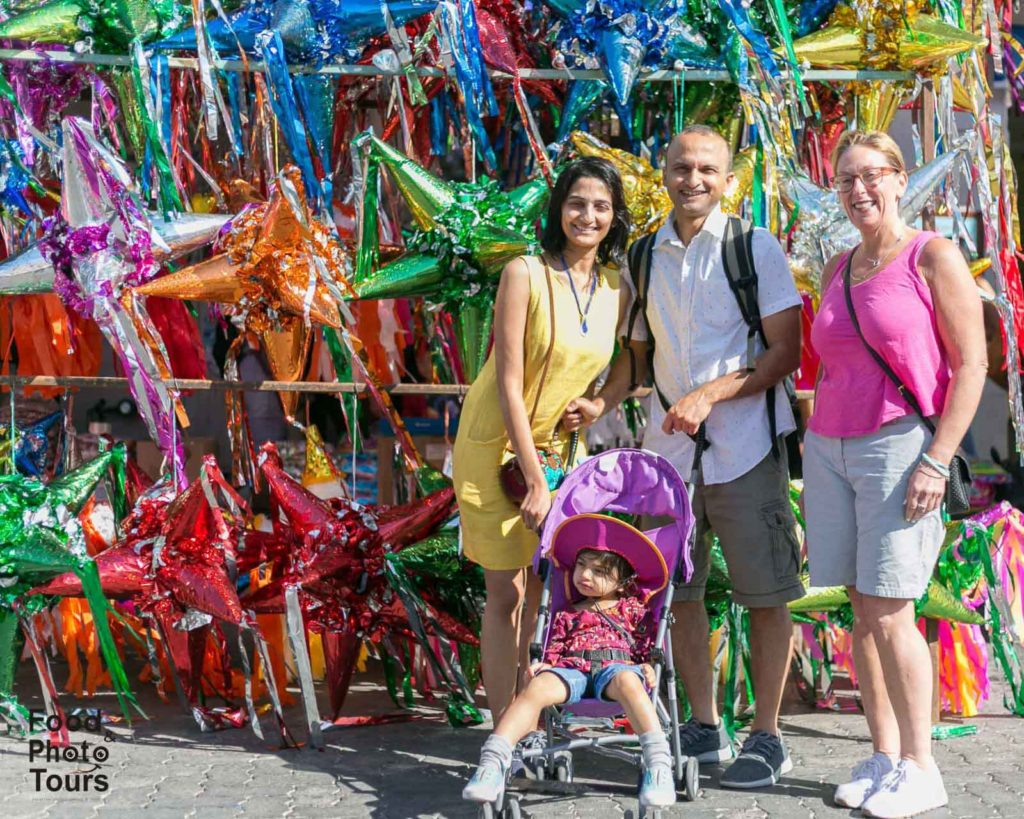 American tourists taking a Food Tour in Pitillal and posing in front of a bunch of piñatas . tour created by Food and Photo Tours in Puerto Vallarta.