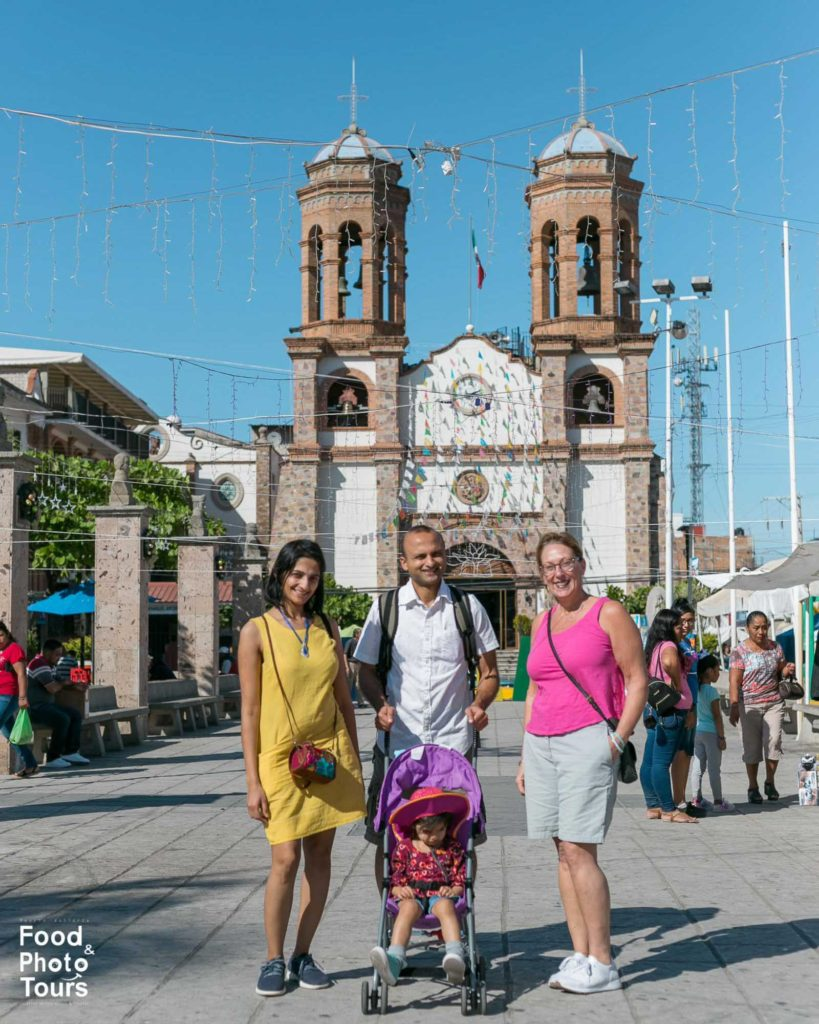 American tourists taking a Food Tour in Pitillal and posing in front of a church, Puerto Vallarta.
