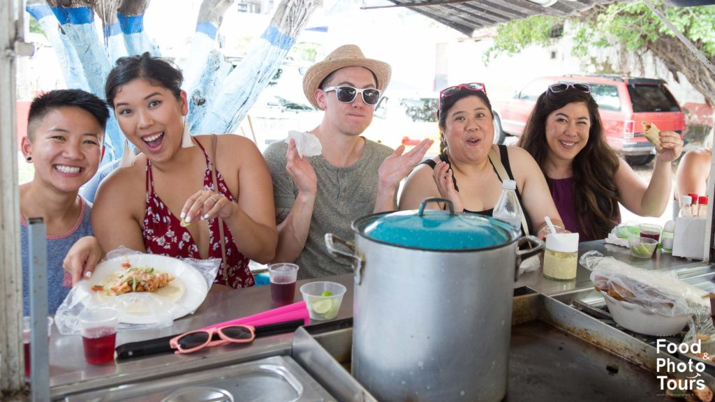 Group of Millenials eating seafood TACOS while on a Taco Tour in Puerto Vallarta created by Puerto Vallarta Food Tours and Photo Tours by Star
