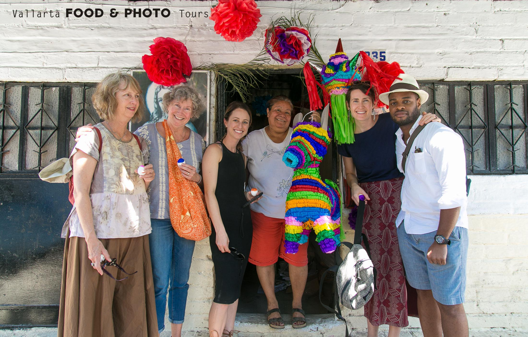 Two American families posing at a piñata shop while taking a Food Tour by Puerto Vallarta Food Tours and Photo Tours, created by Star aka Estrellita Velasco
