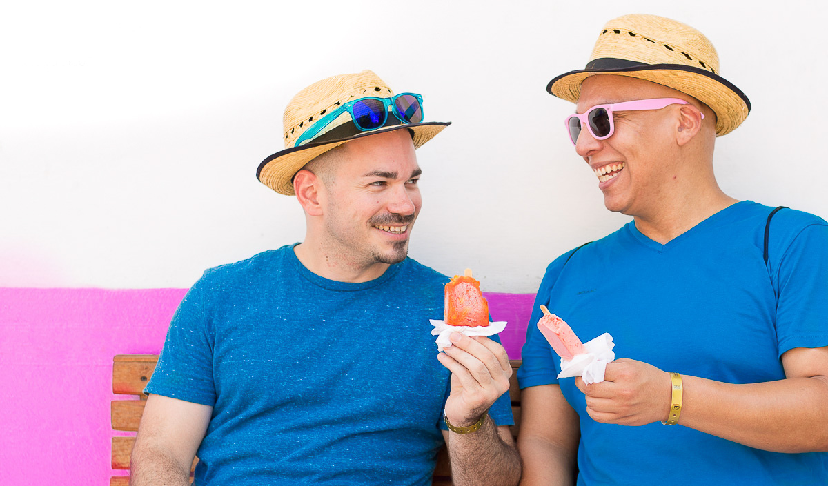 An LGBTQ couple eating popsicles while on a Food Tour in Puerto Vallarta